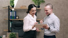 Man and woman look at screen of tablet and lead discussion. Happy male and female look at screen of tablet and lead discussion stock footage
