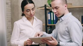 Man and woman look at screen of tablet and lead discussion. In office stock video footage