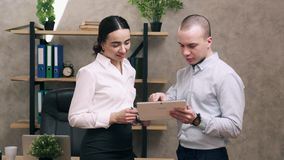 Man and woman look at screen of tablet and lead discussion. In office stock video