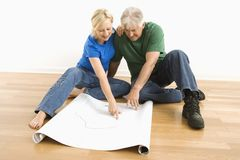 Man and woman looking at blueprints. Royalty Free Stock Images