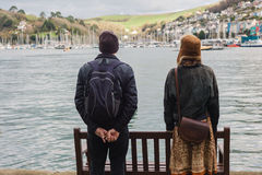 Man and woman looking at boats in village. A young women and a senior men are standing in the harbour of a village and are looking at the water and the boats Royalty Free Stock Photo