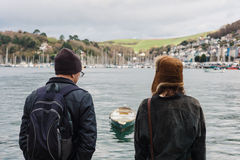 Man and woman looking at boats in village Stock Photography