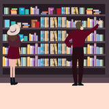 Man woman looking for books at library together around book shelf standing.  Royalty Free Stock Image