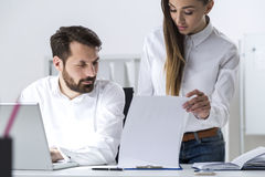 Man and woman looking at clipboard Royalty Free Stock Photography