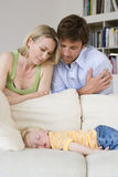 Man and woman looking at daughter (12-15 months) asleep on sofa, close-up Royalty Free Stock Photography