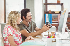Man and woman looking at digital camera in office Stock Photos