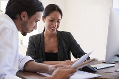 Man and woman looking at documents in an office, close up. Man and women looking at documents in an office, close up Royalty Free Stock Photo