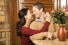 Man and woman looking at each other. Caucasian woman with arms around Caucasian man smiling at each other in kitchen Royalty Free Stock Photography