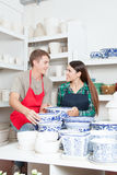 Man and woman looking at each other in a ceramics shop Royalty Free Stock Images