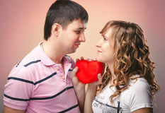 Man and woman looking at each other and holding red heart between Royalty Free Stock Photography