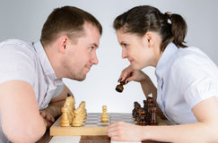 Man and woman looking at each other playing chess Stock Photo