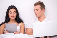 Man and woman looking at each other's computers Royalty Free Stock Image