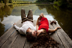 Man and woman are looking at each other on a wooden bridge over Royalty Free Stock Images