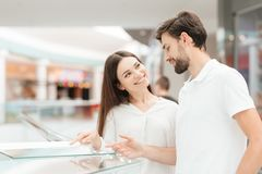 Man and woman are looking at jewelry in kiosk in shopping mall. stock image