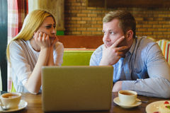 Man and woman Looking at the laptop. They are saddened and distressed. Man and women Looking at the laptop. They are saddened and distressed Stock Photo