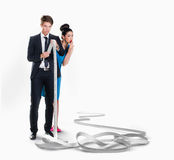 Man and woman looking at a long receipt. Man and women looking at a long receipt isolated on white Royalty Free Stock Images
