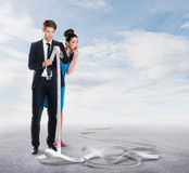 Man and woman looking at a long receipt. Man and women looking at a long receipt outdoors Royalty Free Stock Photo