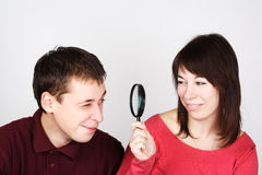 Man and woman looking through magnifier Stock Photo
