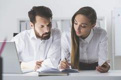 Man and woman looking at notes Stock Photo