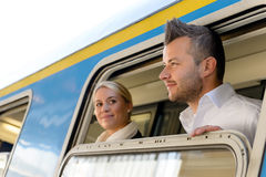 Man and woman looking out train window Stock Photo