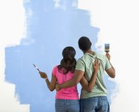 Man and woman looking at paint job. royalty free stock images
