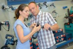 Man and woman looking at power tools. Man and women looking at power tools man royalty free stock images