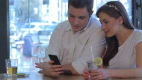 Man and woman looks at the smartphone. Caucasian man and young woman looking at man's smartphone. Handsome man showing something on his phone to brunette girl stock video footage