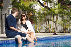 Man and Woman Lounging Beside a Pool - Horizontal Stock Photo