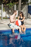 Man and Woman Lounging Beside a Pool - Vertical Stock Images