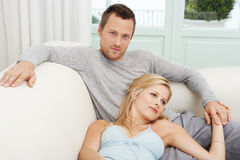 Man and Woman Lounging on Sofa Stock Images
