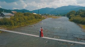 Man and woman in love on a bridge over the river. Aerial shot stock image