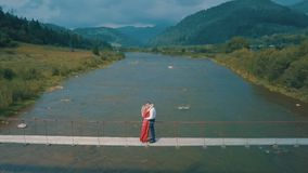 Man and woman in love on a bridge over the river. Aerial shot stock photos