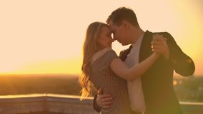 A man and a woman in love dance standing on the roof of a building at sunset looking at each other