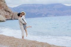 A Man and woman in love enjoying together near sea, running by the beach, laughing, kissing stock photography