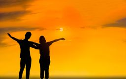 Man and woman in love. They are standing and see the sun set. Woman wearing a hatand man Man hugging woman.Photo concept Silhouette and love Royalty Free Stock Photos
