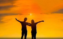 Man and woman in love. They are standing and see the sun set. Woman wearing a hatand man Man hugging woman.Photo concept Silhouette and love Stock Photo