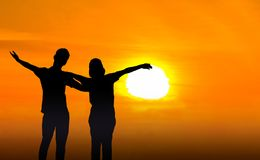 Man and woman in love. They are standing and see the sun set. Woman wearing a hatand man Man hugging woman.Photo concept Silhouette and love Stock Photos
