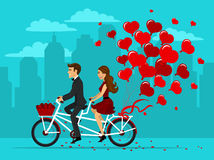 Man and woman in love riding a tandem bike with balloons as hearts Stock Photo