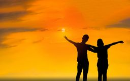 Man and woman in love . Silhouette photo. Man and woman in love. They are standing and see the sun set. Woman wearing a hatand man Man hugging woman.Photo Royalty Free Stock Images