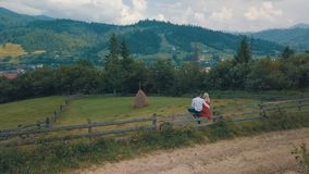 Man and woman in love sit on the fence near the village in the mountains stock images