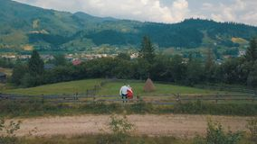 Man and woman in love sit on the fence near the village in the mountains stock photography