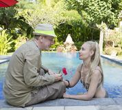 Man and woman, loving couple, at the pool in a garden with tropical trees.   man gives to the woman a flower Stock Photography