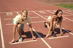 Man and woman low start position running surface stadium. Running competition or gender race. Faster sportsman achieve. Man and women low start position running royalty free stock photos