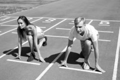 Man and woman low start position running surface stadium. Running competition or gender race. Faster sportsman achieve. Man and women low start position running royalty free stock photo