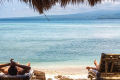 A man and a woman is lying on a deck chair against blue ocean Royalty Free Stock Images