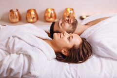 Man and woman lying down on massage beds at luxury spa and wellness center. Beautiful couple relaxing in spa center lying on massage table Stock Photo