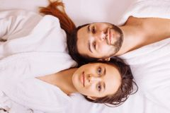 Man and woman lying down on massage beds at luxury spa and wellness center. Beautiful couple relaxing in spa center lying on massage table Royalty Free Stock Photos