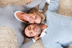 Man and woman lying head to head on the carpet Royalty Free Stock Photos