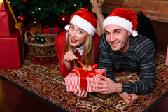 Man and woman lying near the Christmas tree Stock Photography
