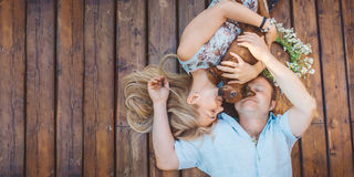 Man and woman lying on a terrace with their dog. Stock Photos